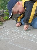 child drawing a chalk on asphalt