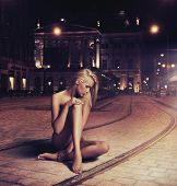 image of nudity  - Naked young woman in sensual pose on the street - JPG