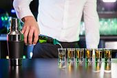 Bartender pouring cocktail into shot glasses at bar counter in bar poster