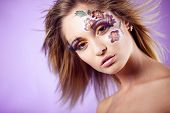 Beautiful fashion model with face-art make-up and blond hair