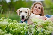 Girl with her dog posing in spring grass