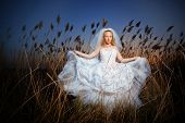 Bride posing showing her wedding dress in rush brushwood