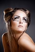 Fashion model with halloween make-up and hairstyle on grey studio background