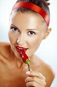 Beautiful woman with red lips holding chilli pepper