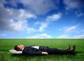 Business man sleeping on a grass field
