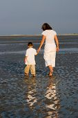 Mother And Son Walking At The Beach