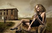 girl sitting on armchair with glass of wine in the countryside
