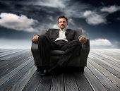 Постер, плакат: деловой человек сидя на кресле против неба
