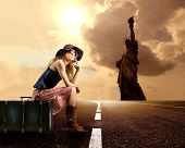 girl doing hitchhiking on the road and the statue of liberty on the background