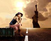 menina fazendo pedindo carona na estrada e a estátua da liberdade em segundo plano