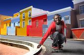 black boy practicing skateboard in a colorful african town