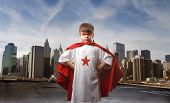 child in super hero costume and city on the background