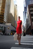 attractive girl in red dress with shopping bags crossing a city street
