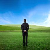 Hombre parado en el medio de un prado verde y observando el panorama delante de él