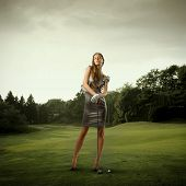 foto of snob  - Portrait of a stylish beautiful woman holding a golf club on a green meadow - JPG