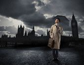 Portrait of a gentleman with an umbrella standing in front of the Big Ben