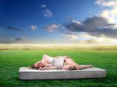 Portrait of a woman lying on a mattress on a green field