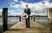 Businessman standing on a dock and holding a lifebelt