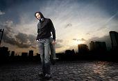 Joven en street-wear de pie en una calle de la ciudad