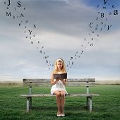 foto of girl reading book  - Young woman sitting on a park bench and reading a book with letters flying away from it - JPG