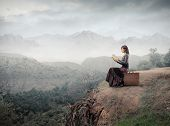 foto of fantasy landscape  - Woman sitting on a suitcase and reading a book with landscape on the background - JPG