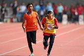 KUALA LUMPUR - AUGUST 15: Malaysia's visually impaired athlete Siti Najihah running with a guide at the track and field event of the fifth ASEAN Para Games on August 15, 2009 in Kuala Lumpur, Malaysia.