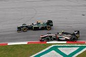 KUALA LUMPUR - APRIL 4: Jarno Trulli of the Lotus team (left) leads Bruno Senna of the HRT F1 team o