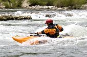whitewater kayak paddler surfing a wave on grade 3 rapid