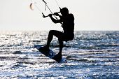 silhouette of a kitesurfer jumping in the waves