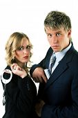 A man with a gun and a woman with handcuffs, both in a suit