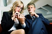 A secretary filing the nails of her boss while he is smoking
