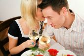 Young couple romantic dinner: both holding white whine glasses, she is whispering something; focus o