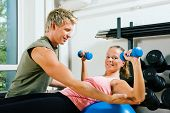 Woman lifting dumbbells on a fitness ball in a gym assisted by her personal trainer