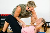 Woman doing sit-ups for her fitness in the gym assisted by her personal trainer