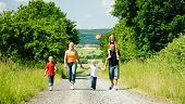 Family walking down a path on a bright summer day, a village in the background