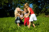 Family (mother with two kids) on a sunlit meadow