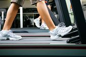 Two people (male / female) working out on a treadmill in a gym