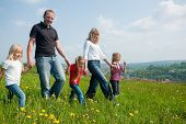Happy family with Children walking down a meadow with dandelion flowers at a bright spring day, in t