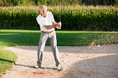 Mature or senior couple playing his ball out of a sand trap, ball in motion and lots of sand frozen