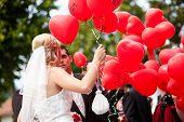Glückliches Hochzeitspaar, sie halten Luftballons mit guten Wünschen in ihre Hände auf sie geschrieben und