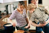 Family cooking in their kitchen - mother stirring some spaghetti sauce, son and father yearning for