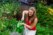 Žena zahradník, zalévání květin v její zahradě v létě