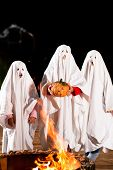 Three very, very scary spooks - kids dressed as ghosts - on Halloween or for carnival or a costume party in front of a fire; FOCUS IS ON PUMPKIN