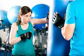 foto of sandbag  - Woman Boxer hitting the sandbag - JPG