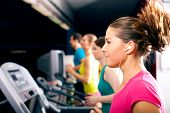 Running on treadmill in gym - group of women and men exercising to gain more fitness, the woman in f