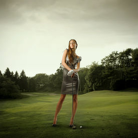 stock photo of snob  - Portrait of a stylish beautiful woman holding a golf club on a green meadow - JPG