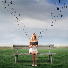 picture of sitting a bench  - Young woman sitting on a park bench and reading a book with letters flying away from it - JPG