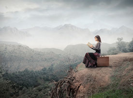 pic of fantasy landscape  - Woman sitting on a suitcase and reading a book with landscape on the background - JPG