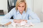 Sulking woman sitting in her office in front of an shattered piggy bank with less in than expected
