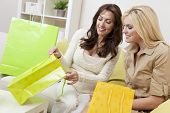 Two beautiful women friends at home looking in shopping bags together